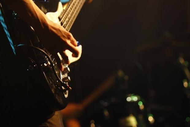 初心者セットの楽器でライブをするベーシスト
